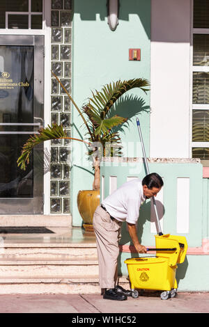 Miami Beach Florida Ocean Drive Art Deco Historic District Hispanic man janitor job working cleaning mop bucket wring hotel en - Stock Image