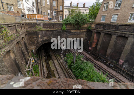 Railway cutting of the formwer Widened Lines between buildings near King's Cross Station, London, UK - Stock Image