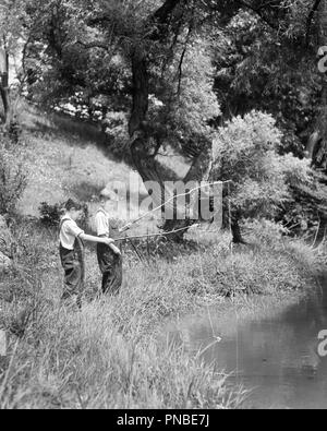1930s TWO BOYS FISHING WITH STICK AND STRING FISHING RODS ON BRIGHT SUMMER DAY - a2495 HAR001 HARS LEISURE AND RECREATION SIBLING FRIENDLY ANGLING BIB OVERALLS GROWTH JUVENILES PRE-TEEN PRE-TEEN BOY RODS TOGETHERNESS BLACK AND WHITE CAUCASIAN ETHNICITY HAR001 OLD FASHIONED - Stock Image