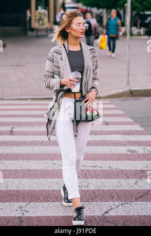 Beautiful gril with blonde hair and glasses crosses the street with a cup in the hand - Stock Image