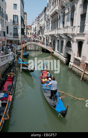 Bridge over canal Rio de la Canonica and gondalas with gondalier and sunshine Venice Italy - Stock Image