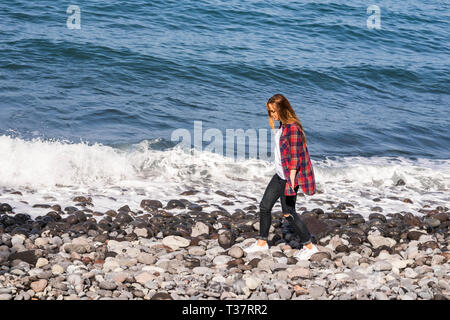 Young hipster style girl walk on the rocks near the waves of the ocean - outdoor leisure activity and vacation alone concept for beautiful people in s - Stock Image
