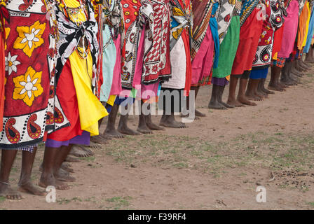 A line of barefoot Masai Women wearing the traditional shawls called Kangas, in a village near the Masai Mara, East - Stock Image