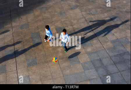 Two boys playing soccer with a brightly colored ball (football) - Stock Image