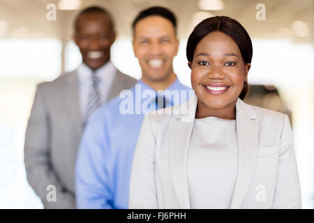 vehicle sales team standing in a row inside car showroom - Stock Image