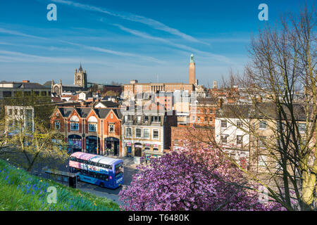 Norwich city skyline with spires of St. Peter Mancroft church and City hall tower and tourist bus passing by, viewed from Castle hill. Norfolk, UK. - Stock Image