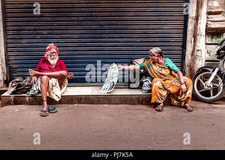 Senior citizen woman reading newspaper and senior citizen man sitting nearby. The photo was taken in Summer in city of Ahmedabad - Stock Image