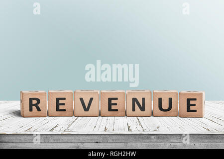 Revenue sign on a wooden desk with a light blue wall in the background - Stock Image