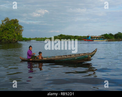 Mother and child in canoe on Kampong Phluk River returning to home in stilted village of Kompong Phluk Siem Reap Cambodia Asia only access to village  - Stock Image