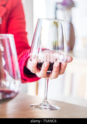 Woman hand holding a glass of red wine at wine tasting in Setubal wine region, Portugal. - Stock Image