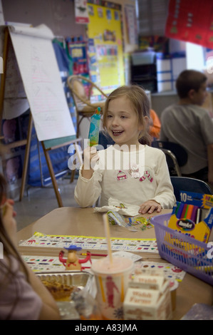 A first grader finishes her lunch at school - Stock Image