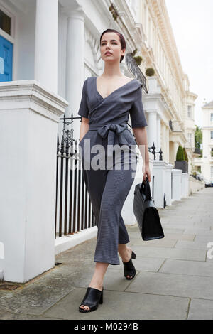 Chic businesswoman in jumpsuit walking in street, low angle - Stock Image
