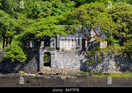 Secluded small house with a walled garden set in woodland on an river estuary. - Stock Image