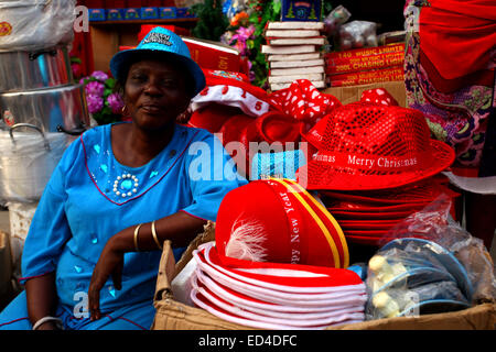 Hat Vendor seating by her wares during the Xmas celebration - Stock Image