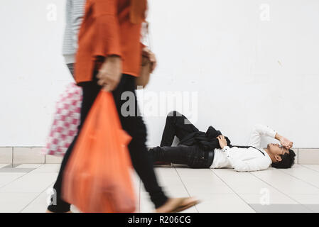 young asian businessman lying down at walkway thinking of his problem and look so depressed while people passing by ( motion blur ) - Stock Image