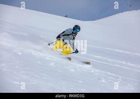 A skier riding off piste in fresh powder after hiking to the summit of La Capa. - Stock Image