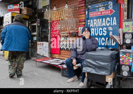 A street scene in Jackson Heights Queens, New York featuring a daydreaming salesman and a passerby. On 82nd Street - Stock Image
