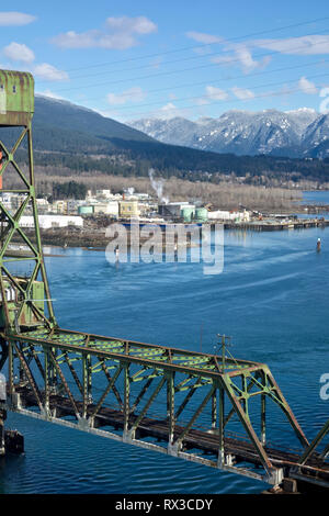 Train bridge crossing Burrard Inlet from Vancouver to North Vancouver Ironworkers Memorial Bridge).  ChemTrade chemical plant is seen in North Van. - Stock Image