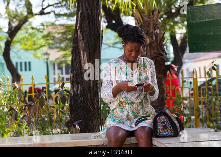Beautiful Young Creole Woman with Dark Skin Sitting in Pretty Flower Dress Listening to Music and Text Messaging on Mobile Device - Stock Image