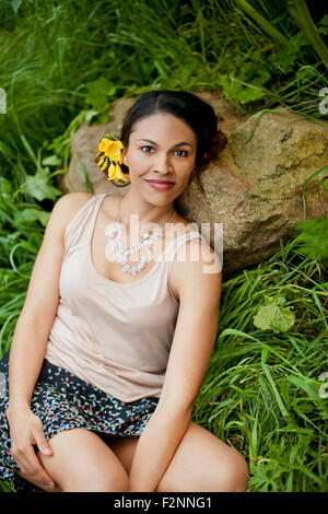 Mixed race woman laying on rock in tall grass - Stock Image