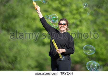 Beautiful middle age woman playing with soap bubbles outdoor during the daytime. She looks at the camera and smiles.  Concept about simplicity in life - Stock Image
