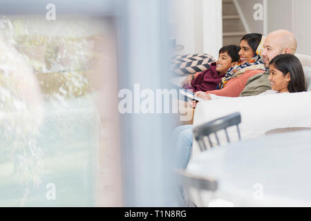 Family watching TV on living room sofa - Stock Image