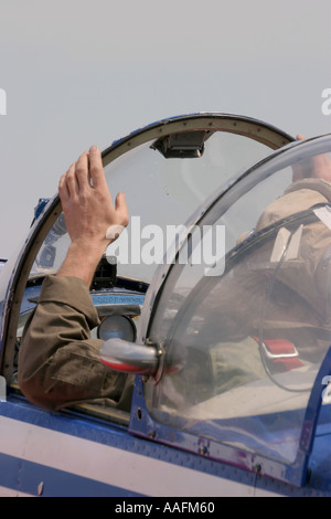 Pilot is waiting in cockpit with left hand on windscreen seal - Stock Image