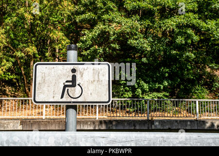 Dirty handicap sign with a wheel chair and green nature in the background - Stock Image