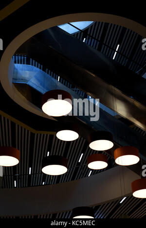 Circular Modern lights hang from the ceiling of a modern building interior - Stock Image