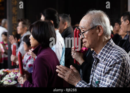 Taipei, Taiwan, Feb. 5, 2019: An old man prays at Longshan Temple in Taipei on Tuesday, Lunar New Year's Day and the first day of the Year of the Pig. Credit: Perry Svensson/Alamy Live News - Stock Image