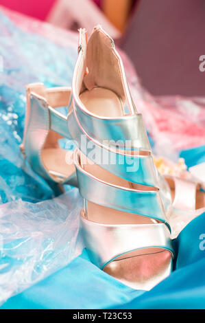 White married shoe on a bright blue fabric - Stock Image