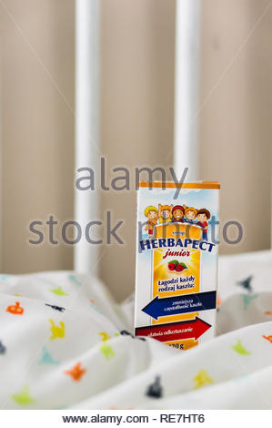 Poznan, Poland - November 8, 2018: Herbapect Junior coughing syrup in a box on a baby bed in soft focus. - Stock Image