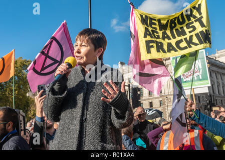 London, UK. 31st October 2018. Green Party MP Caroline Lucas addresses the crowd blocking the roadway in front of Parliament after making the 'Declaration of Rebellion' against the British Government for its criminal inaction in the face of climate change catastrophe and ecological collapse. They listened to speeches by George Monbiot and Green Party MP Caroline Lucas and there were songs and poems. A number of activists brought large wreaths and lay down with them, with several lock-ons. Police tried to clear the road, but the protesters ignored them, taking a show of hands to remain blocking - Stock Image