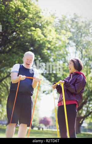 Enthusiastic active senior couple exercising, using resistance bands in sunny park - Stock Image