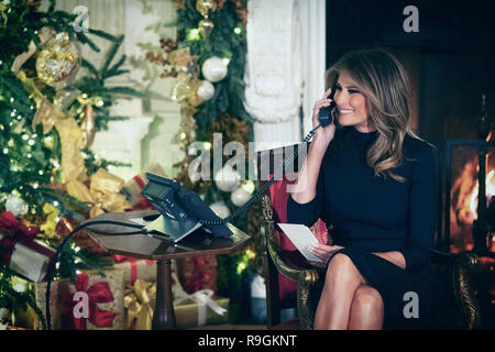 Washington, United States Of America. 24th Dec, 2018. U.S. First Lady Melania Trump smiles as she talks to a young child calling into NORAD Tracks Santa on Christmas Even in the East Room of the White House December 24, 2018 in Washington, DC. The First Lady returned from Palm Beach to join the President who was alone at the White House after shutting down the government in a budget standoff over his border wall. Credit: Planetpix/Alamy Live News - Stock Image