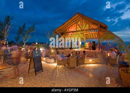 Jamaica Negril Ricks Cafe open air bar viewpoint at sunset Reggae band playing - Stock Image