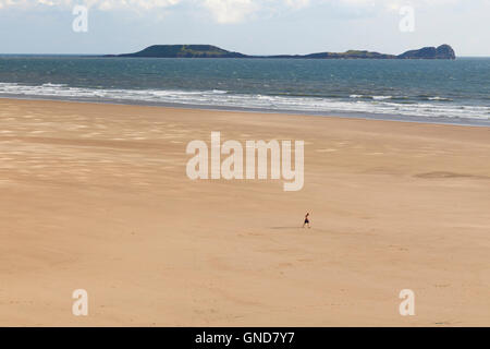 The Worm's Head viewed from Rhossili Beach. - Stock Image