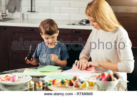 Joyful little boy of 4 years-old learning how to use scissors together with a Mom, cutting out the Easter bunny form colourful paper. Happy family sit - Stock Image