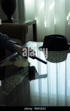 Automatic pistol gun on glass table in bedroom in luxury hotel in silhouette with reflection of window light. - Stock Image