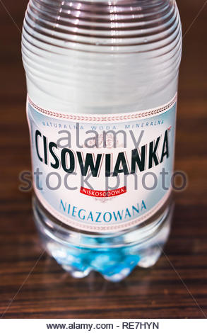 Poznan, Poland - November 17, 2018: Bottom of a Polish Cisowianka natural water bottle on a wooden table in soft focus. - Stock Image