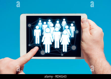 Man holding a tablet device showing social media and communications concept, touching the screen with a finger with blue sky in background - Stock Image