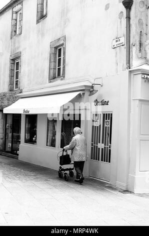 An elderly woman with a wheeled walker in a quiet street in Quimper, Brittany, France. B&W - Stock Image