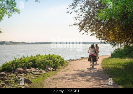 Helsinki island summer, view on a summer morning of two young women riding on a cycle path on Katajanokka Island near Helsinki, Finland. - Stock Image
