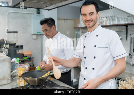 Portrait of young male chef preparing spaghetti with colleague in kitchen. - Stock Image