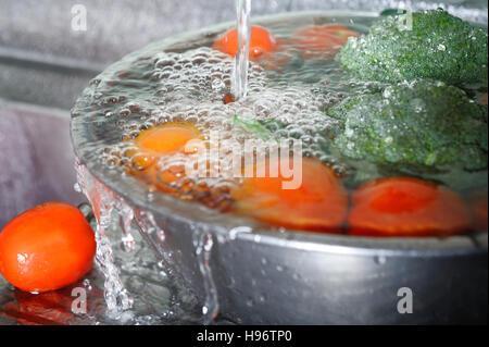washing fresh vegetable in sink - Stock Image