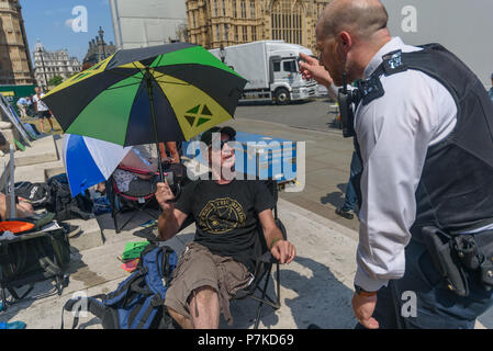 London, UK. 6th July 2018. A police officer questions Jeff who was punched in the face by a man who members of the group 'We The Undersigned Have a Legal Right to use Cannabis' identified as Derek White who they have outed for selling fake cannabis oil to people desperate to cure various conditions.The protest in Old Palace Yard was  in support of Newport West Labour MP Paul Flynn's Private Member's Bill to allow the medical use of cannabis was expected to be debated this afternoon. Credit: Peter Marshall/Alamy Live News - Stock Image