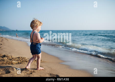A small toddler boy with shorts walking on sand beach on summer holiday. - Stock Image