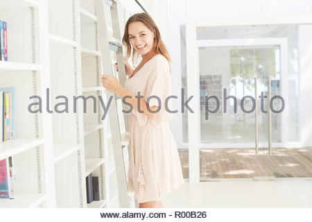 Young woman standing on library ladder - Stock Image