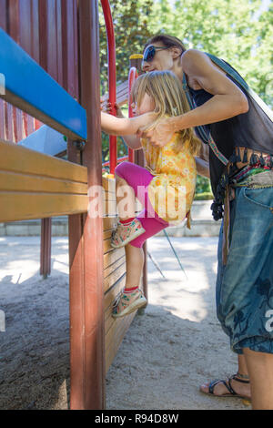 mother woman helping three years old blonde girl, with yellow dress and pink tights, to climb steps in wooden wall in playground, in park of Madrid ci - Stock Image