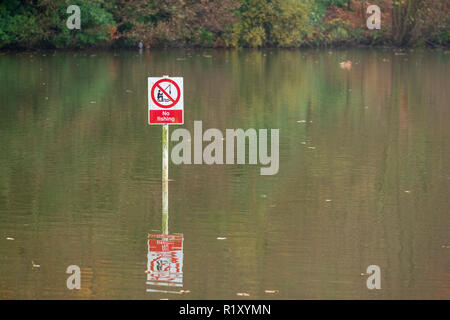 No fishing sign in red circle with white post reflected in pond water - Stock Image